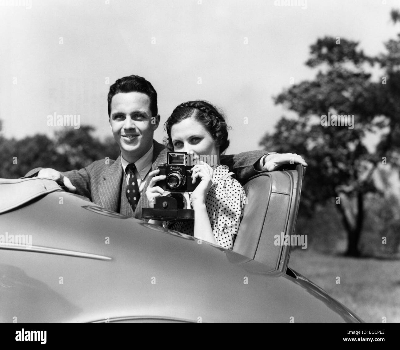 1930s COUPLE SITTING IN JUMP SEAT OF CAR POINTING CAMERA AT VIEWER - Stock Image