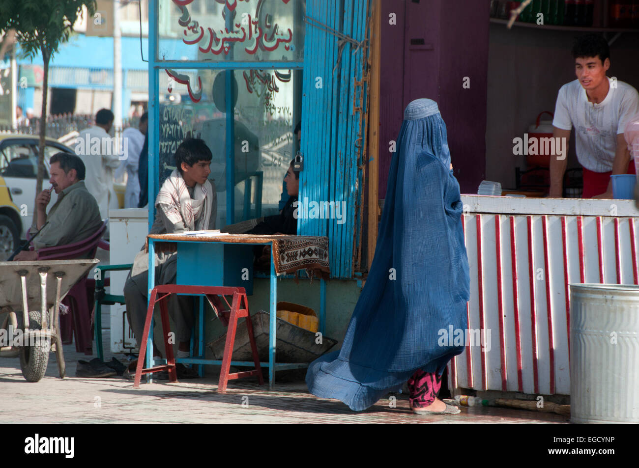 Mazar e Sharif streetscene - woman wearing a burqa buying an ice-cream - Stock Image