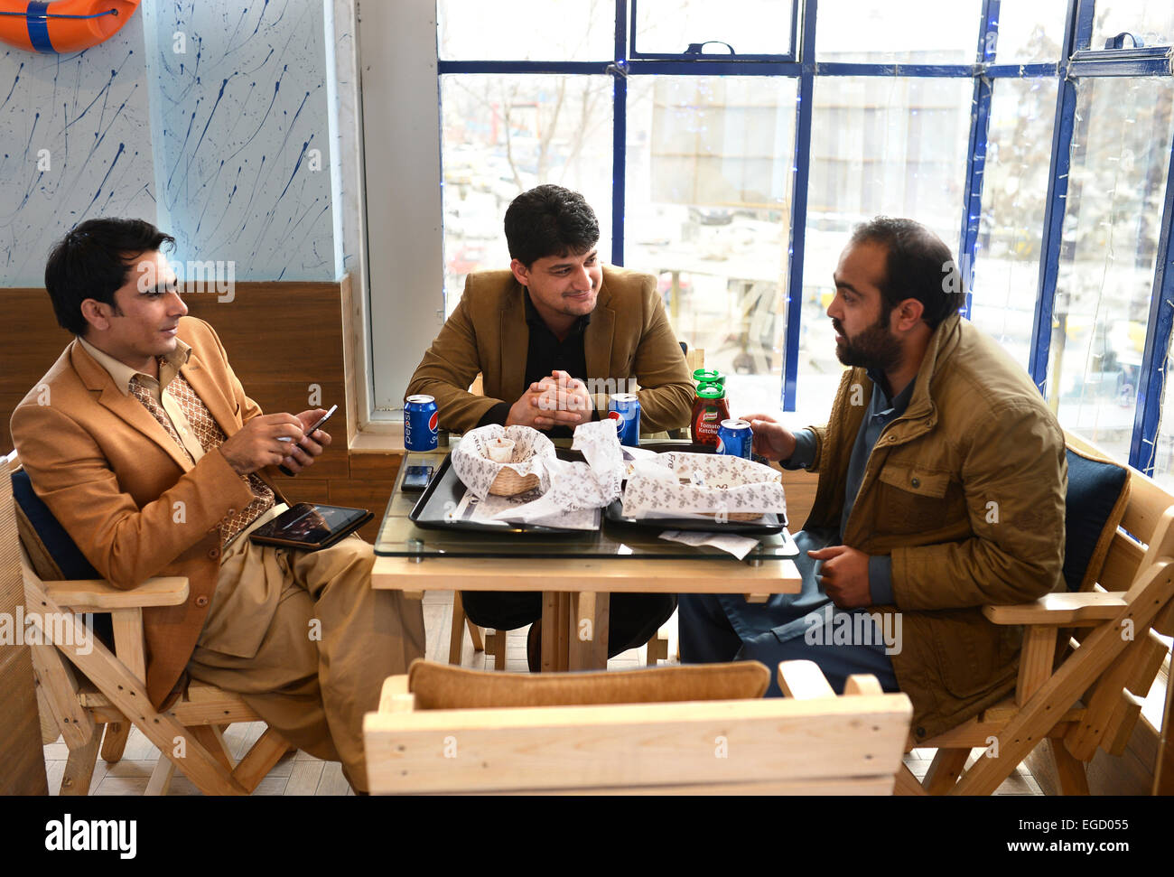 Afghan auditor at a ministry Ahmad Shah Ahmadzai (first from right) eating fish and chips with his friends at the - Stock Image