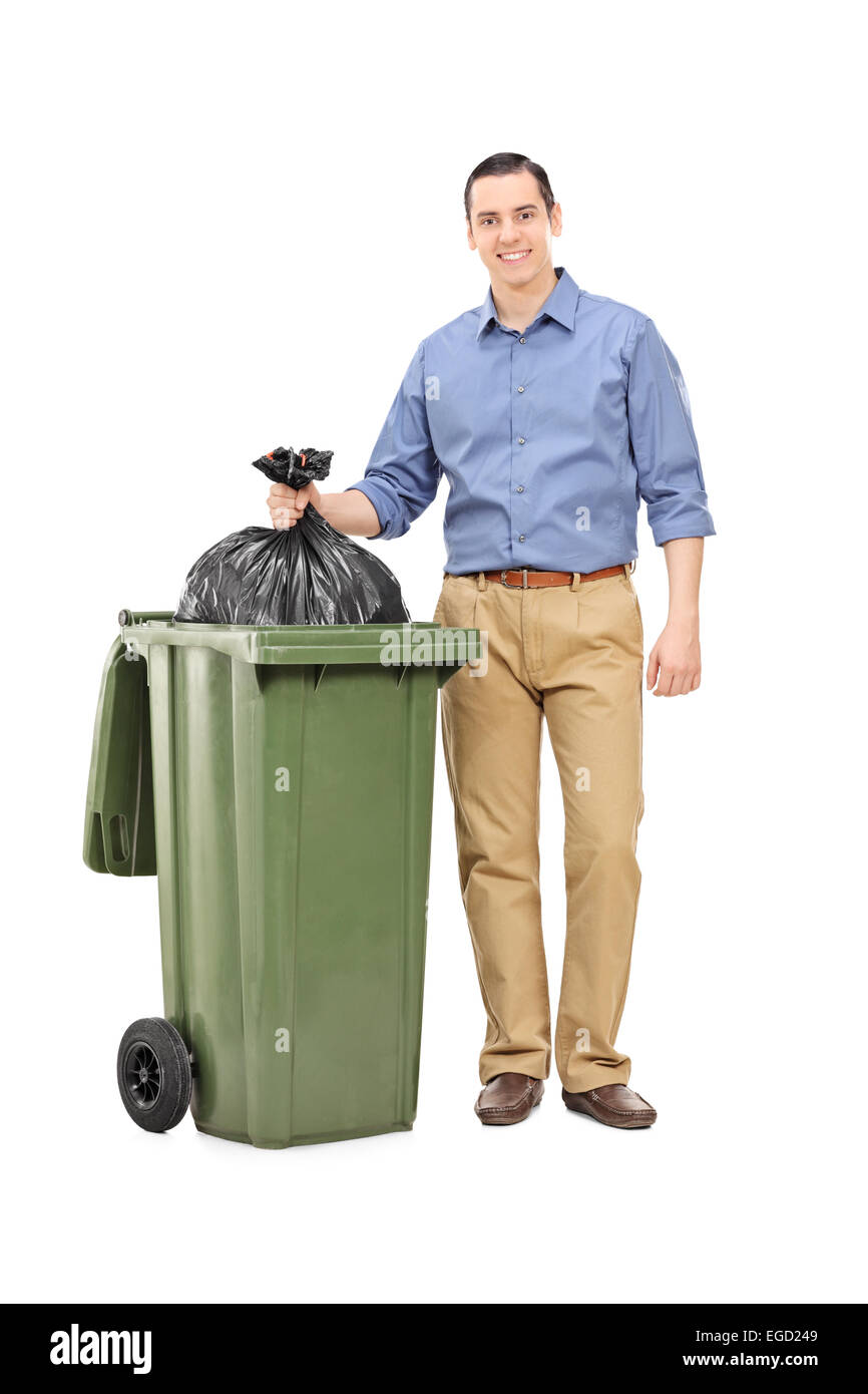 Full length portrait of a man throwing out garbage isolated on white background - Stock Image