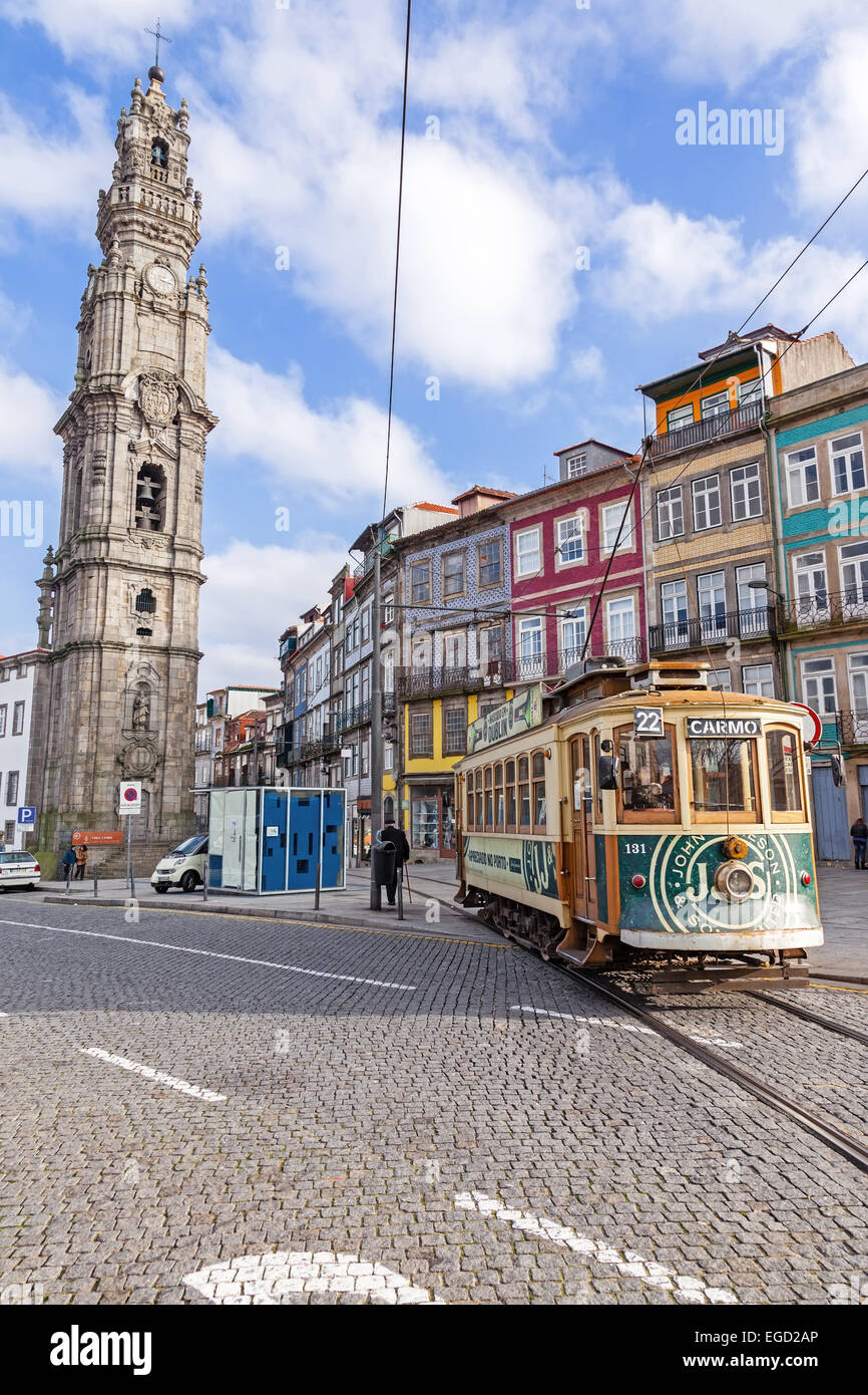Porto, Portugal. The old tram passes by the Clerigos Tower, one of the landmarks and symbols of the city. Stock Photo
