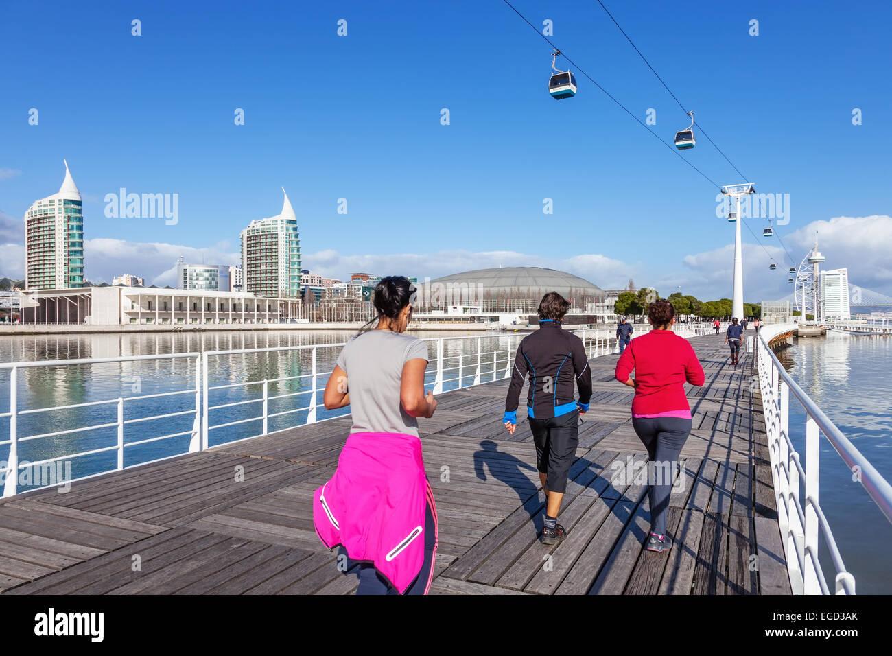People practicing sports on Passeio Ribeirinho. Atlantico Pavilion (MEO Arena). Vasco da Gama Tower and Bridge, - Stock Image