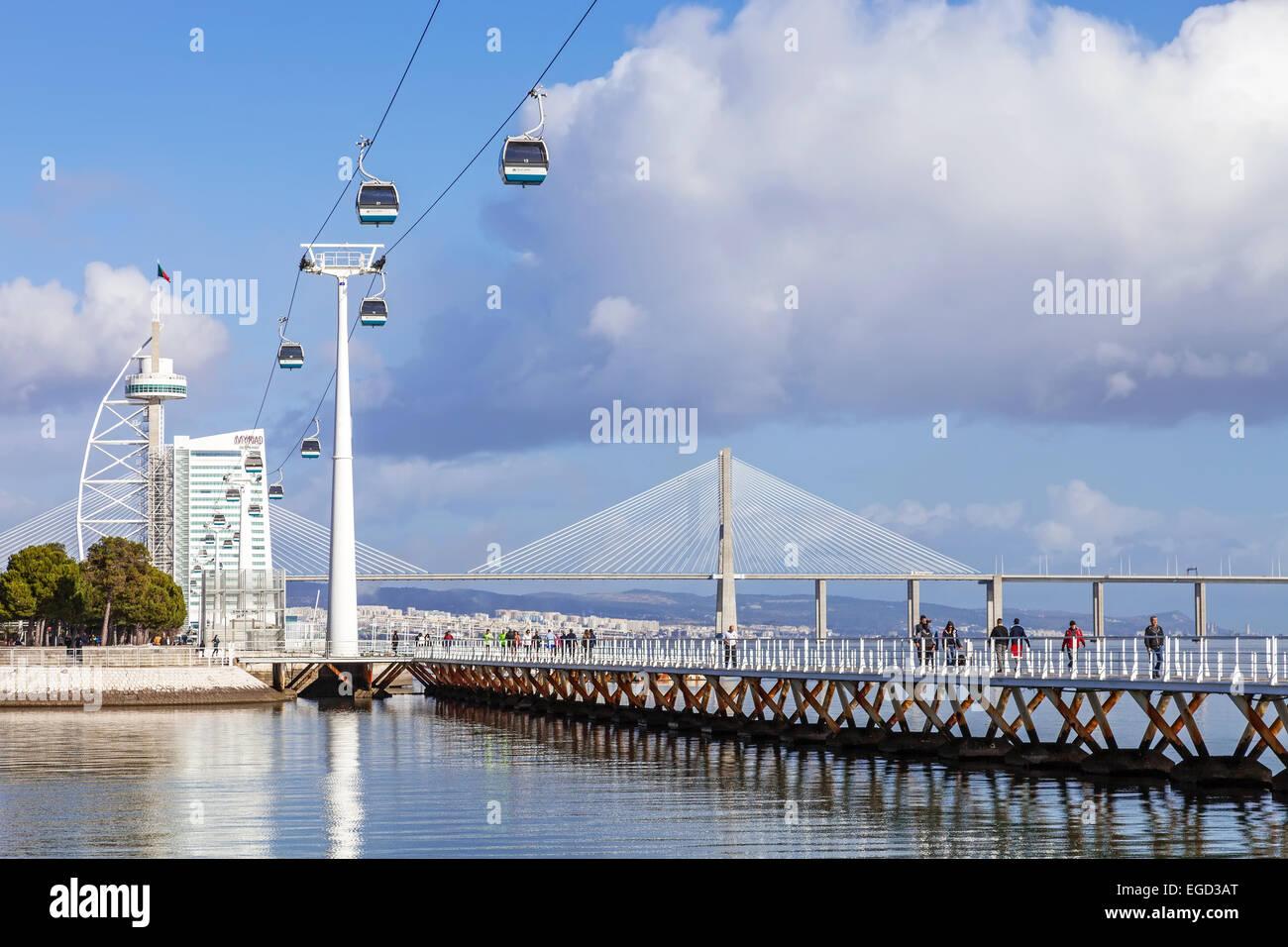 People practicing sports on the Passeio Ribeirinho over the Tagus River. Vasco da Gama Tower and Bridge, Myriad - Stock Image
