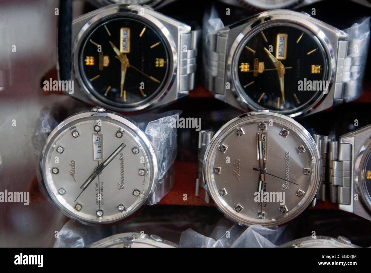 Watches are for sale and displayed in a display case on a city sidewalk in Phnom Penh, Cambodia. - Stock Image