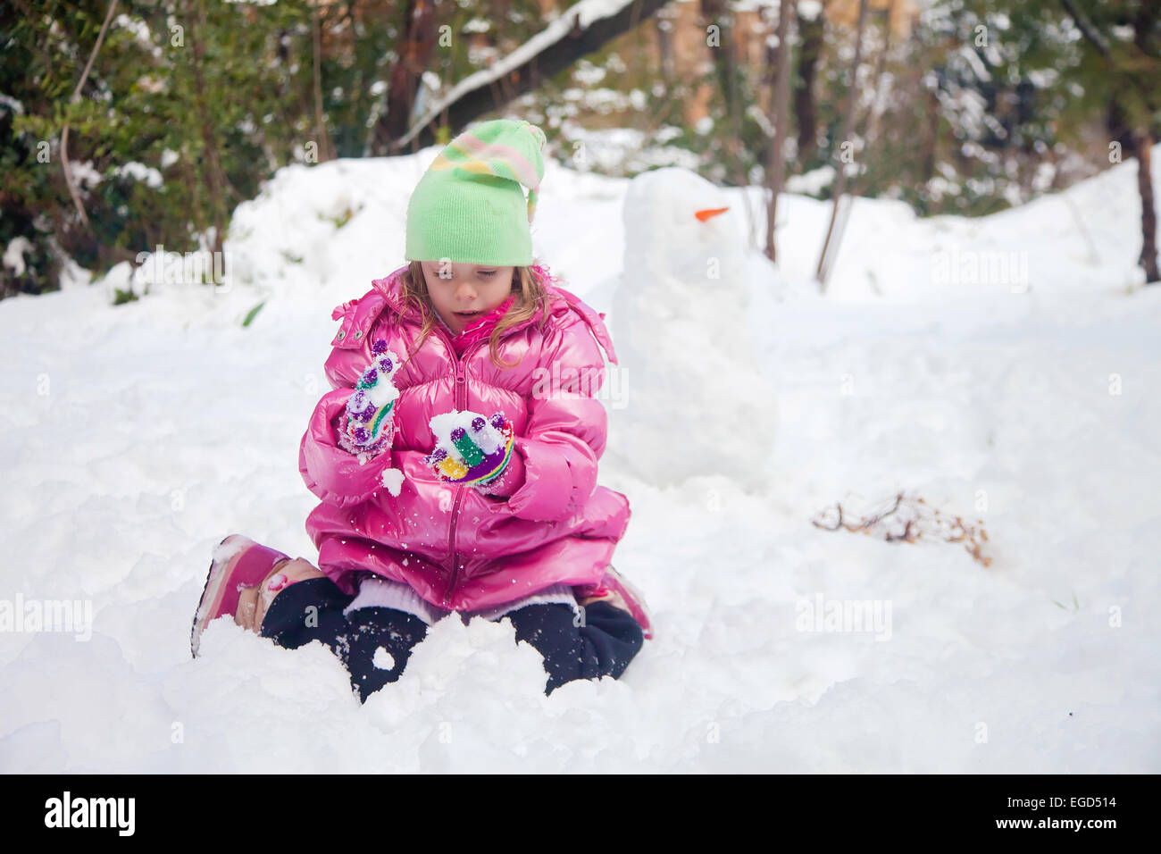Little blonde girl playing with snowflakes in the deep snow in Jerusalem - Stock Image