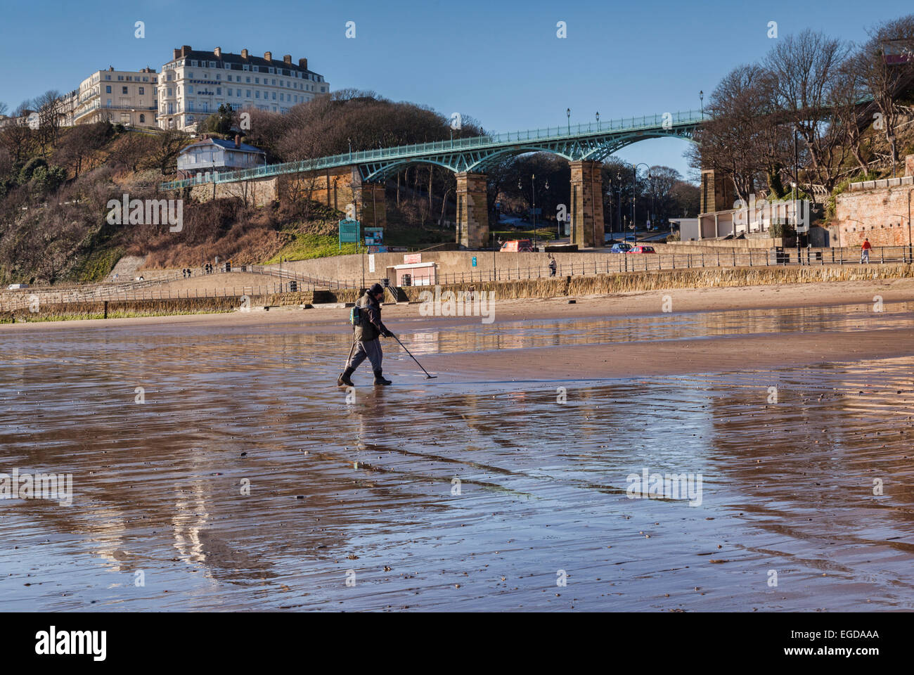 Man metal detecting on Scarborough Beach. In the background are the Spa Bridge and the Esplanade Hotel. - Stock Image