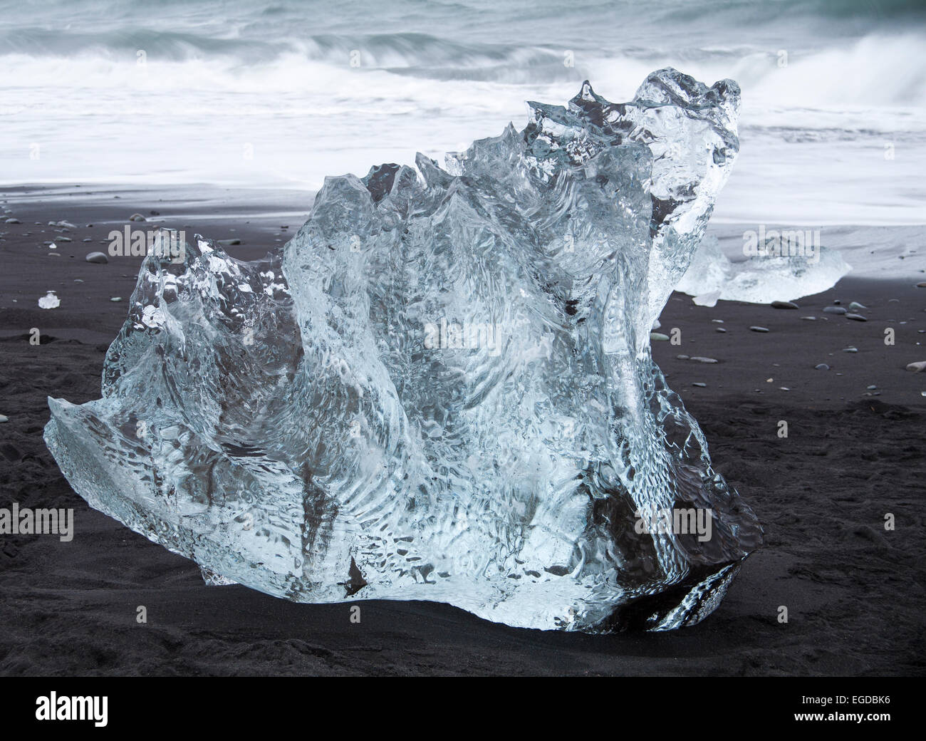 patterned shapely block of ice iceberg contrasting with black sand at Jokulsarlon Glacial beach, Diamond beach, Stock Photo