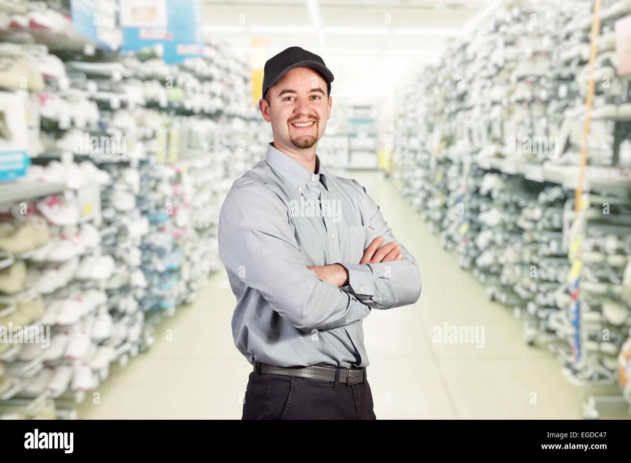 smiling worker in big sport shop - Stock Image