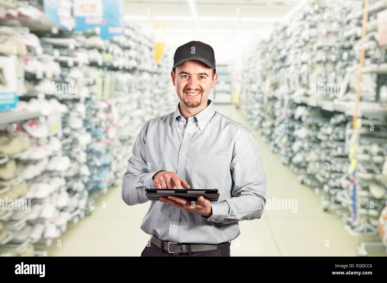 confident worker with tablet and warehouse background - Stock Image