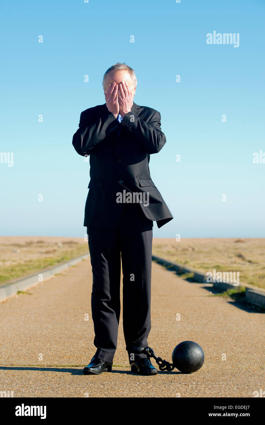 Businessman in dark suit, attached to a ball & chain with his head in his hands. He stands in the middle of - Stock Image