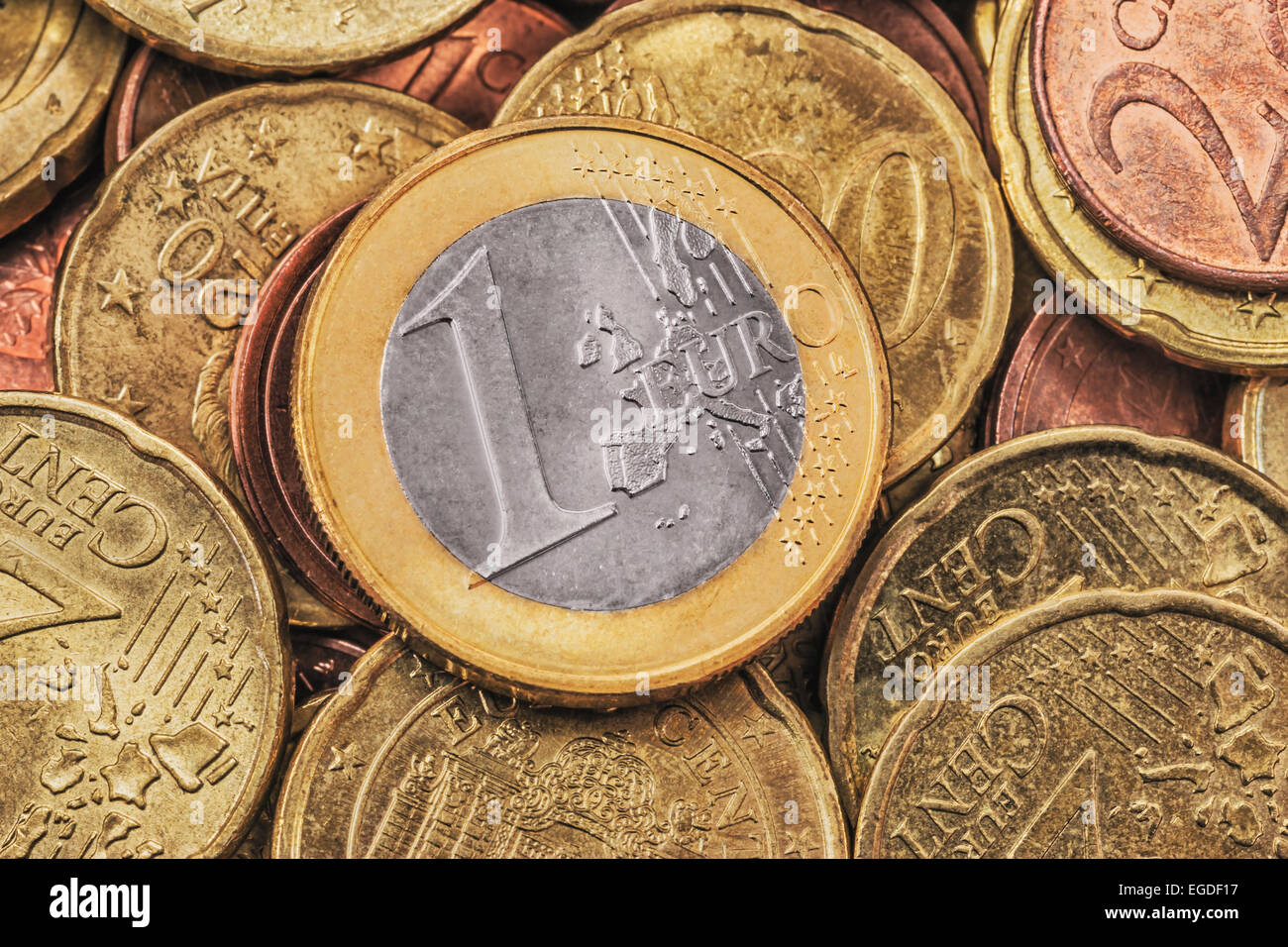 Many Euro coins, on top is a 1 Euro coin, front side - Stock Image
