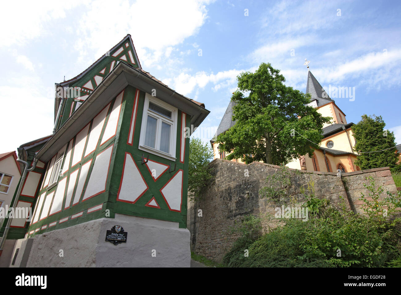 The smallest house and the church of St. Martin, Old town, Bad Orb, Spessart, Hesse, Germany - Stock Image