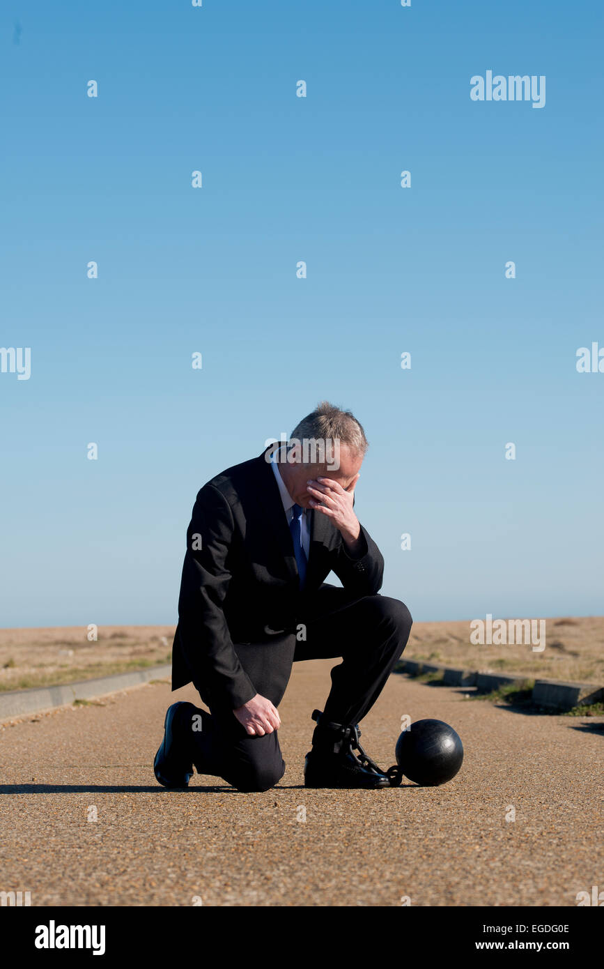 Businessman kneeling in the middle of a long road, head in hand and attached to a ball & chain. - Stock Image