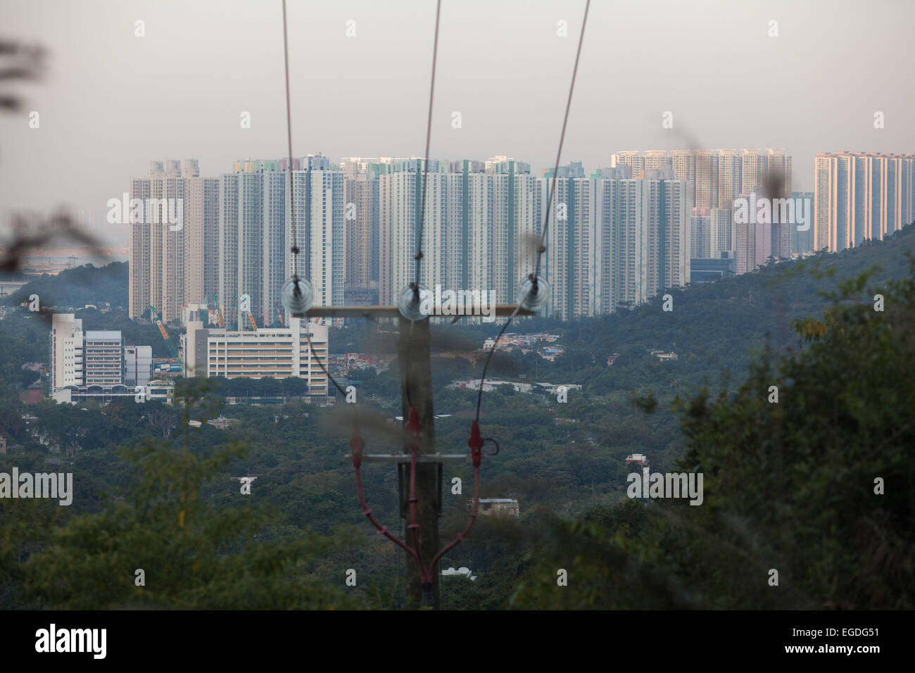 Tung Chung city is part of Hong Kong and is a giant cluster of tall tower blocks. It is surrounded by green hills. - Stock Image