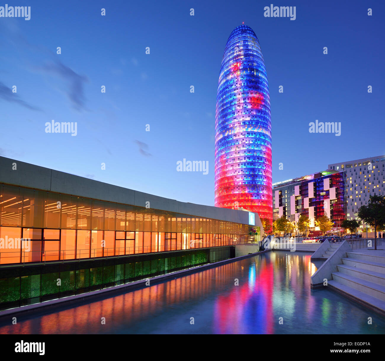 Disseny Hub Barcelona and skyscraper Torre Agbar, illuminated, architect Jean Nouvel, Barcelona, Catalonia, Spain - Stock Image