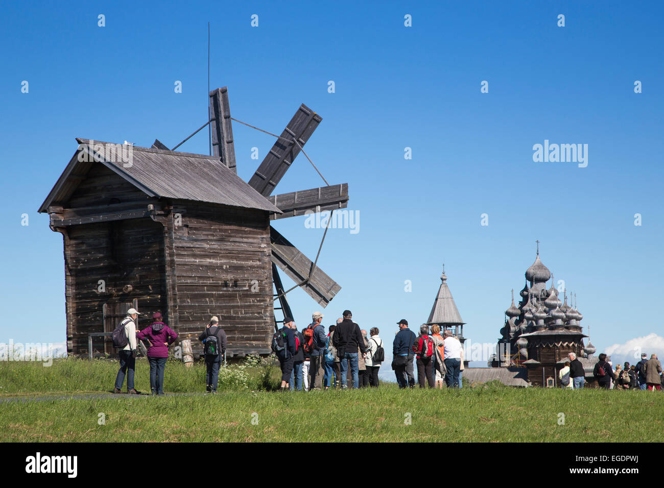 People in front of wooden windmill, belfry and Church of the Intercession of the Virgin and Church of the Transfiguration - Stock Image