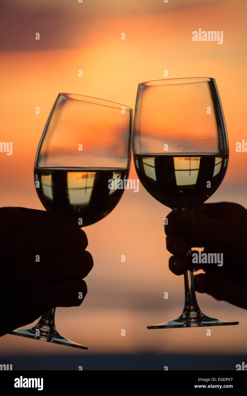 Hands clinking white wine glasses aboard the river cruise ship MS General Lavrinenkov (Orthodox Cruise Company) - Stock Image