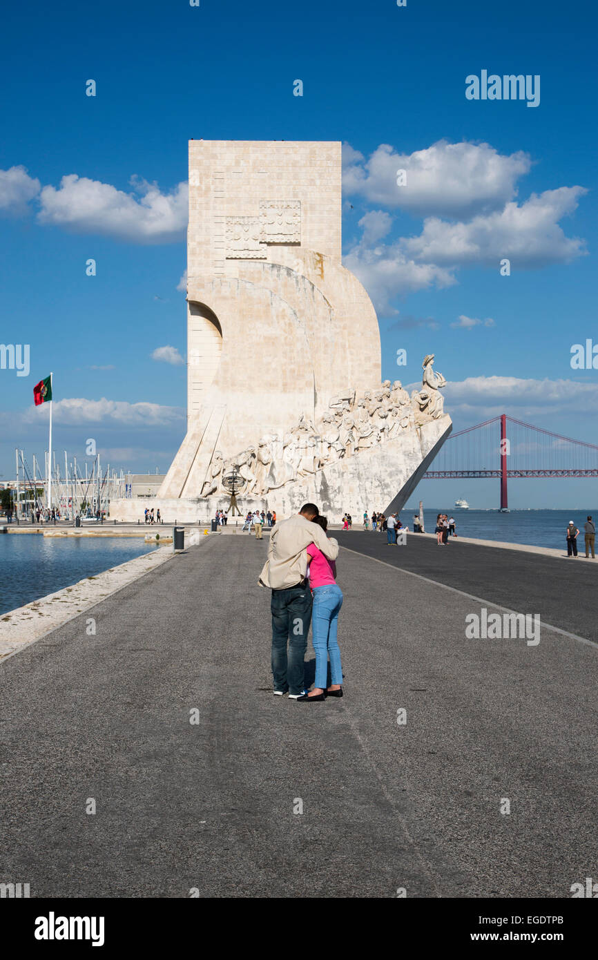 Couple at the Padrao dos Descobrimentos (Discoveries Monument) in Belem with Ponte 25 de Abril bridge over Tagus - Stock Image