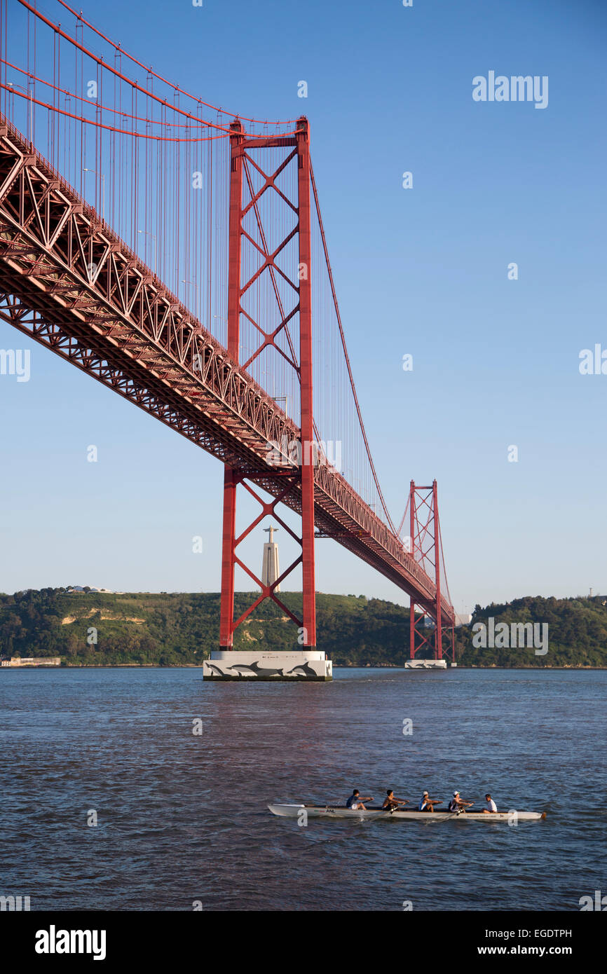 Kayakers paddling under Ponte 25 de Abril bridge over Tagus river with Cristo Rei statue in the background, Lisbon, Stock Photo