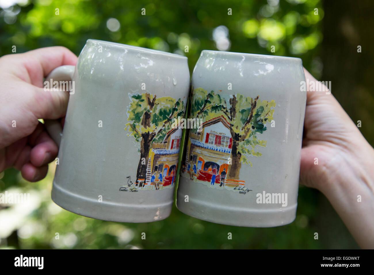 Two beer mugs being clinked together at Entla's Keller beer garden, Erlangen, Franconia, Bavaria, Germany - Stock Image