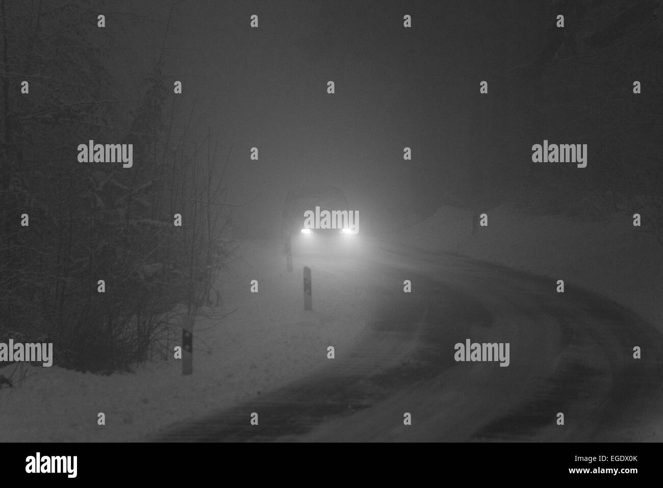 a car driving through the darkness in a foggy & snowy environment - Stock Image