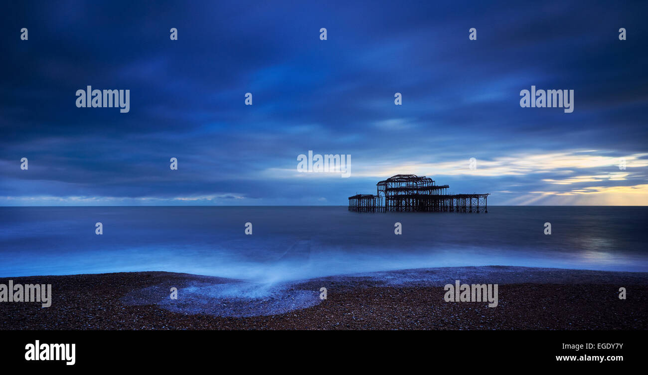 The decaying remains of Brighton's West Pier at sunset with the tide coming in. - Stock Image