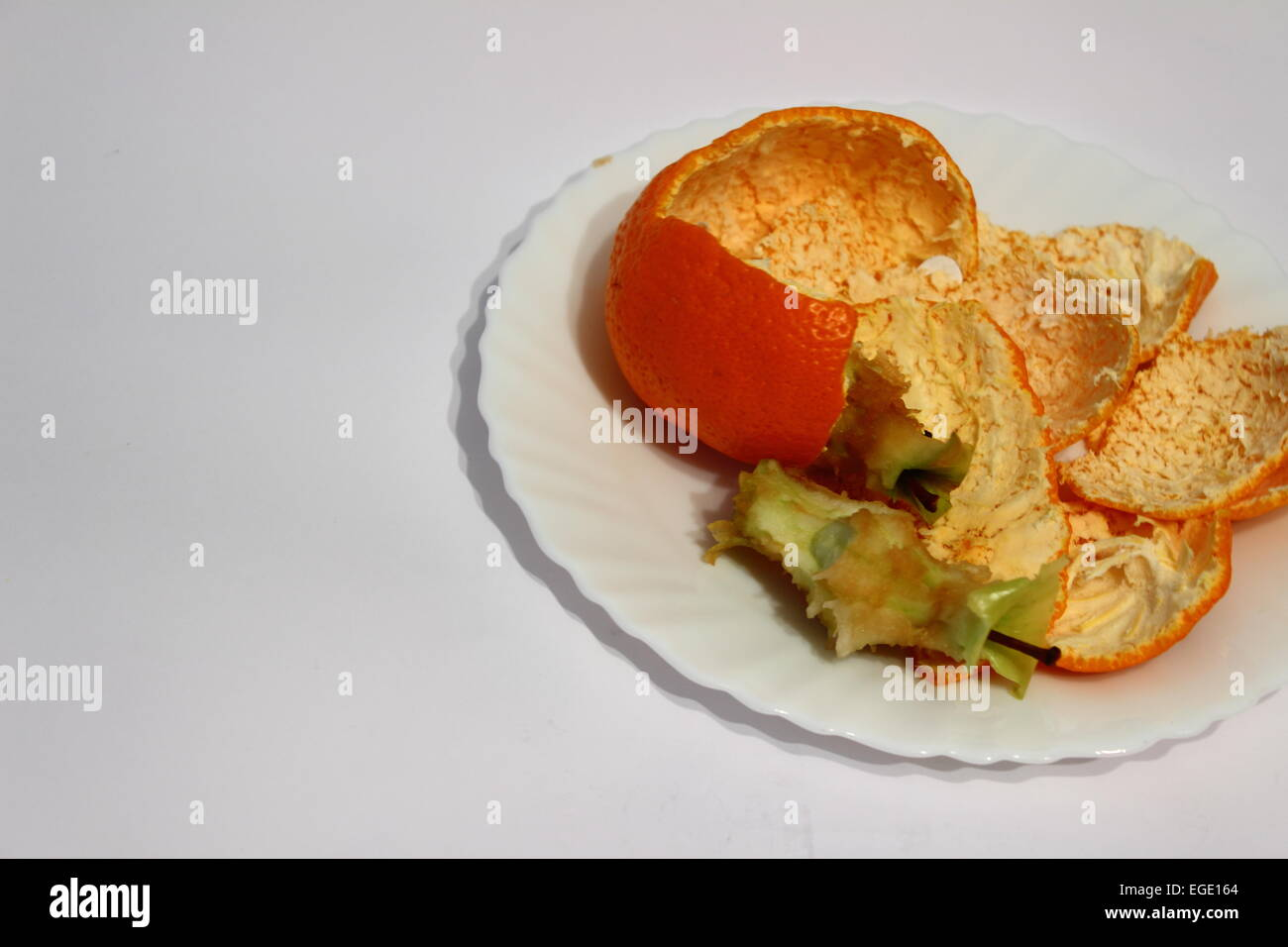 the plate lie the remains of oranges and apples - Stock Image