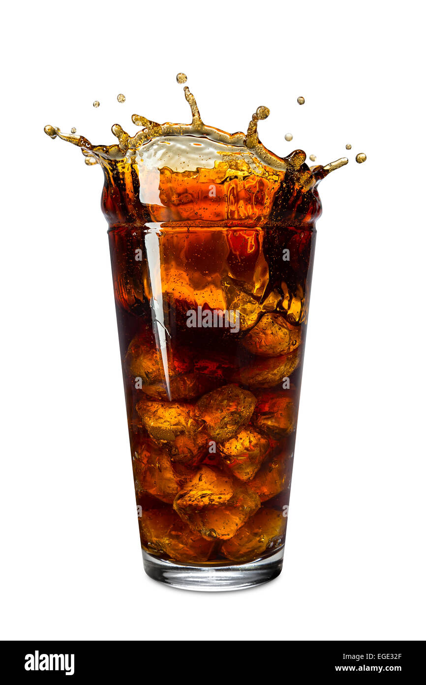 ice splashes into glass of cola - Stock Image