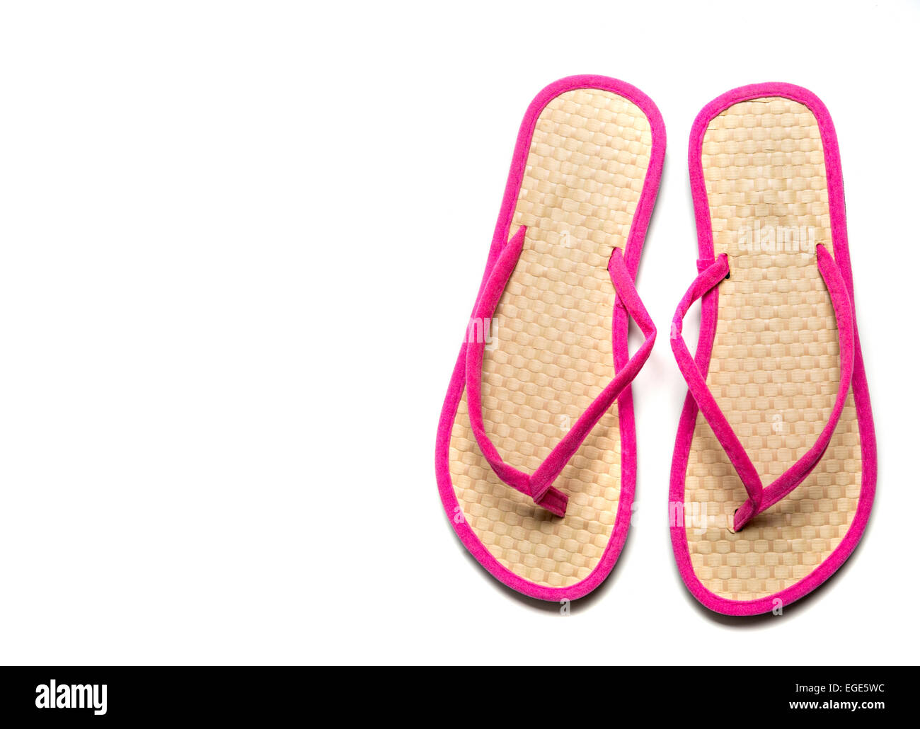 Straw and pink flip-flop sandals on a white background with copy space - Stock Image