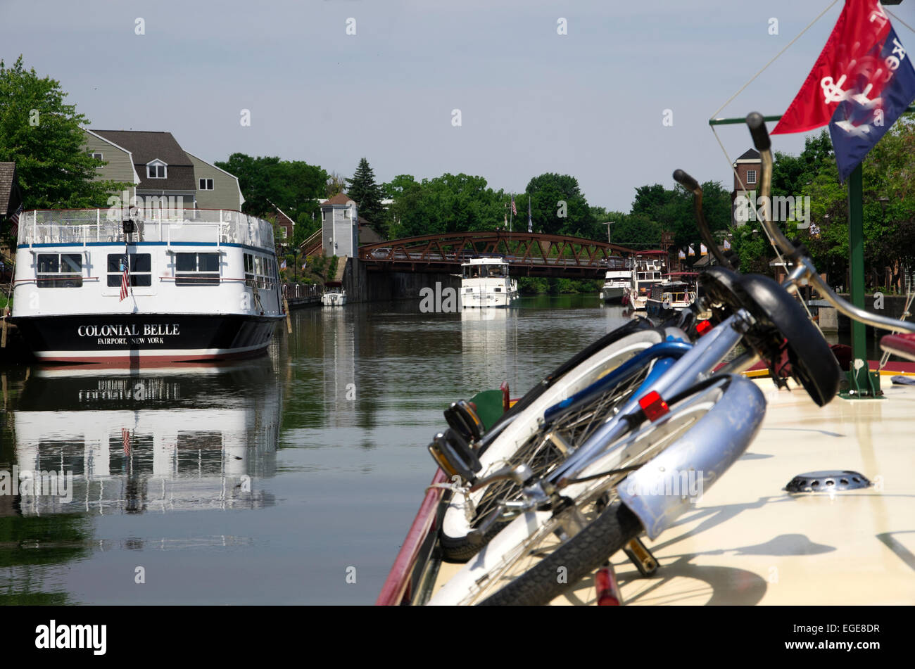 Charter boat and private yacht wait for Fairport angled bridge to open.  Dinner boat tied up. - Stock Image
