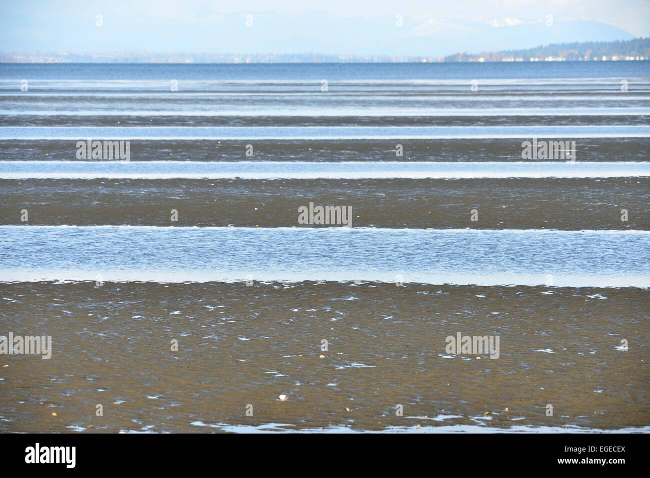 Parallels. A receding tide captures water forming parallel lines - Stock Image