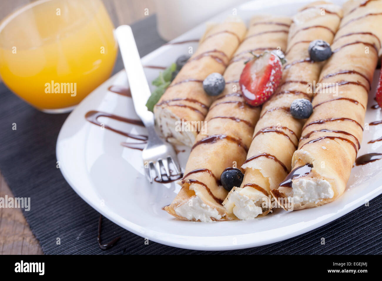 Delicious sweet rolled pancakes on a plate with fresh fruits - Stock Image