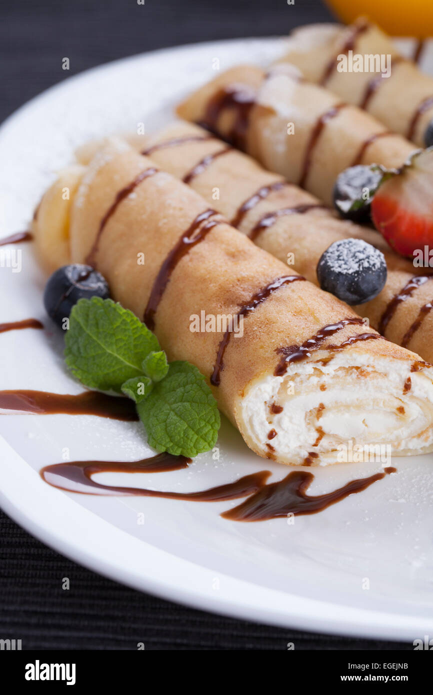 Delicious sweet rolled pancakes on a plate with fresh fruits Stock Photo