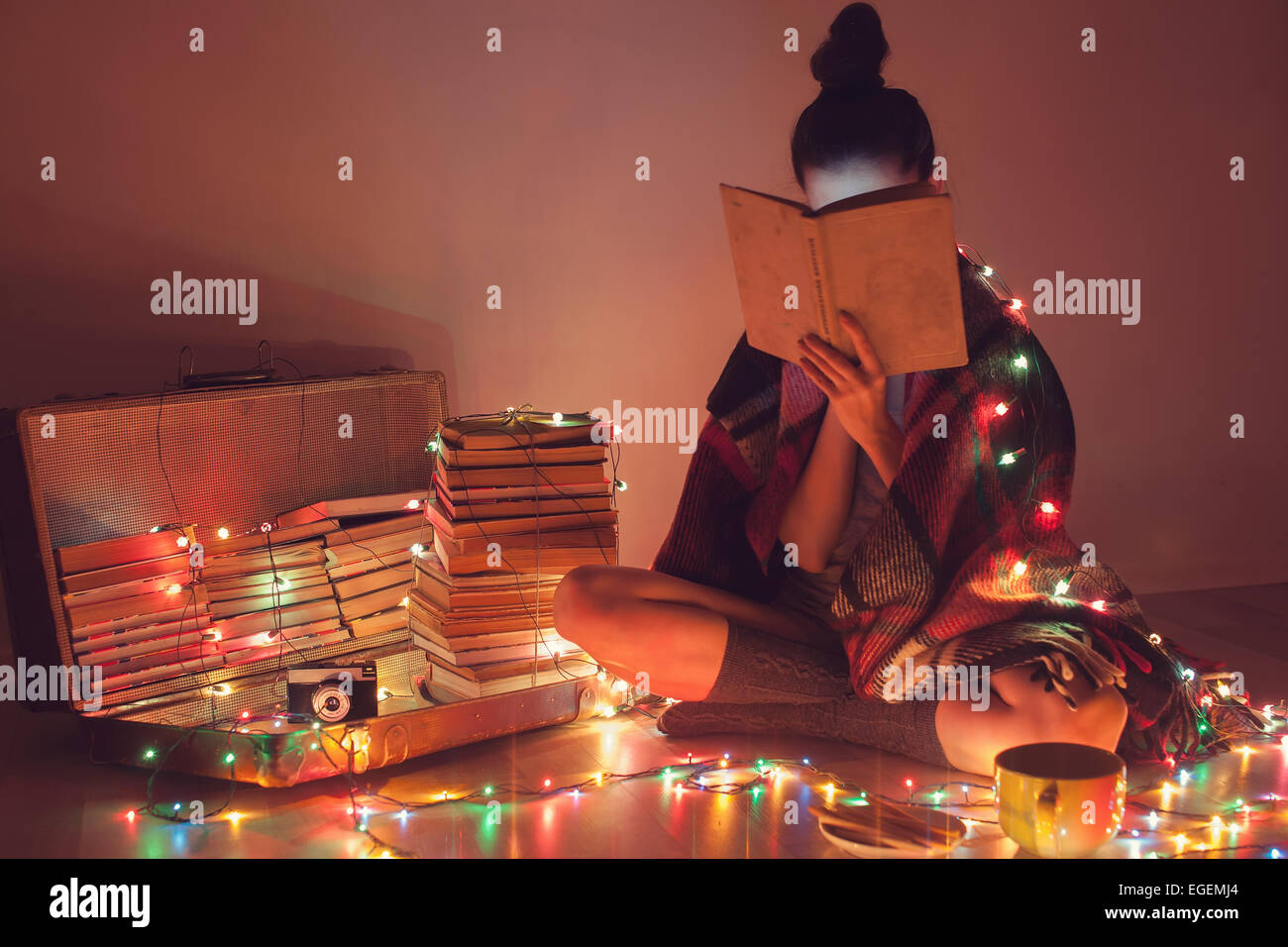 girl reading a book under blanket at home in cold weather - Stock Image