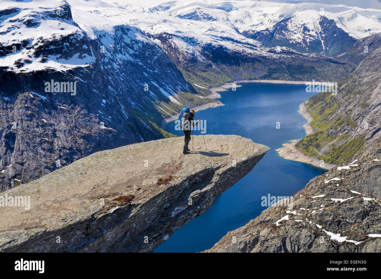Hiker with backpack on Trolltunga rock high above scenic fjord in Norway - Stock Image