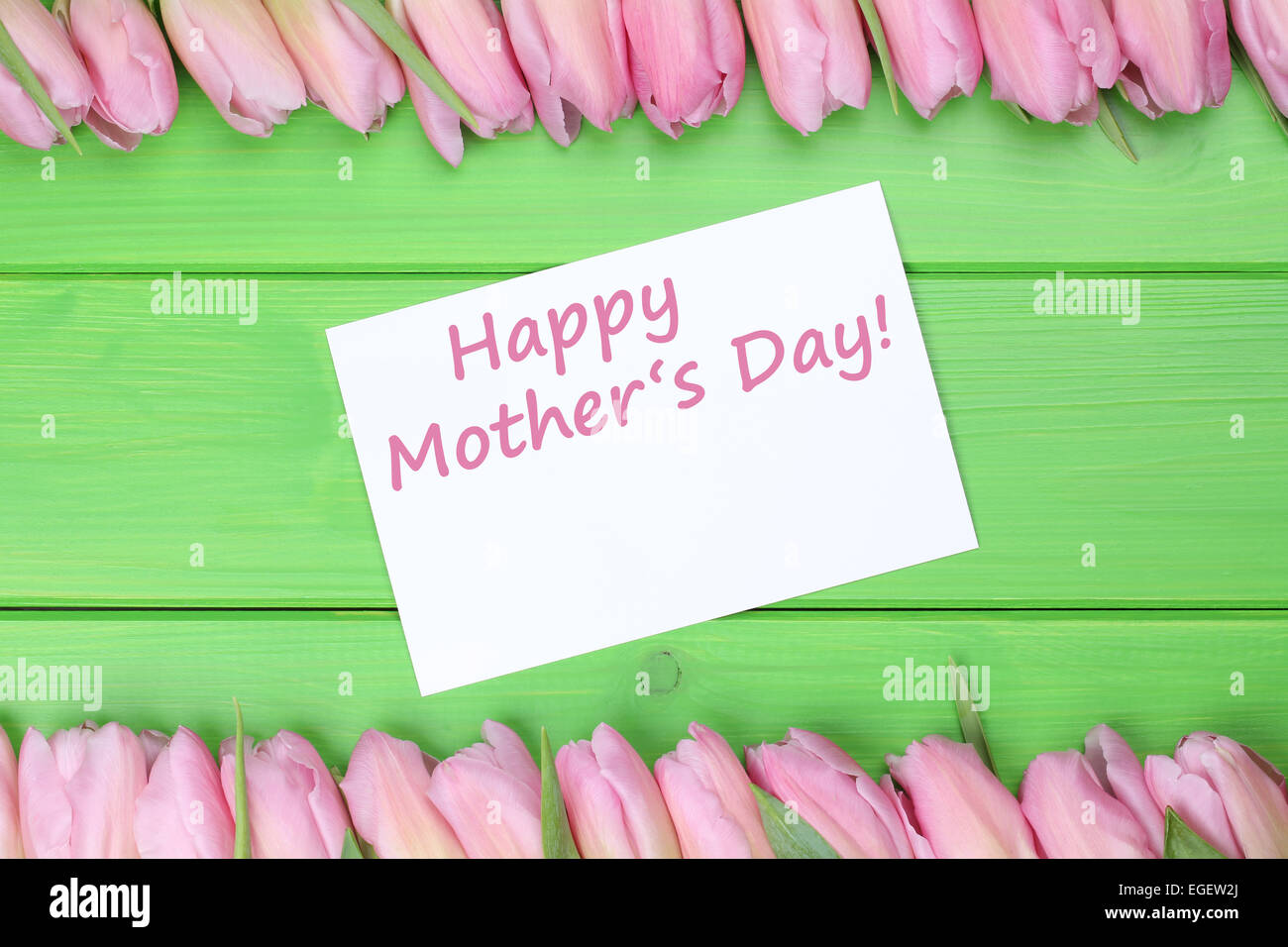 Tulips flowers with greeting card and the text Happy mothers day with copyspace - Stock Image