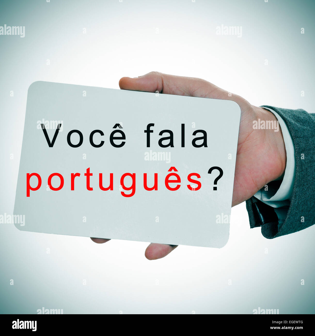 man hands showing a signboard with the sentence voce fala portugues? do you speak portuguese written in it Stock Photo