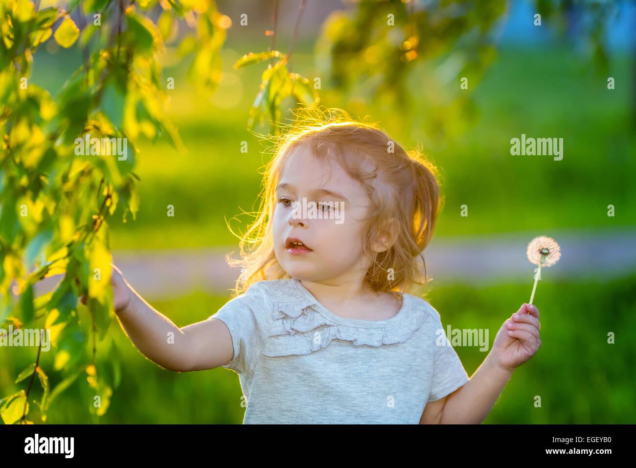 Little girl in spring sunny park Stock Photo