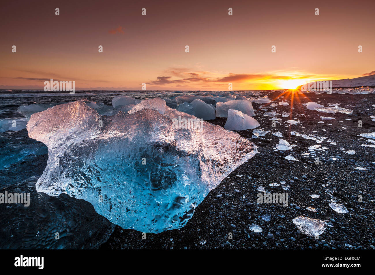 Broken ice from washed up Icebergs on Jokulsarlon black beach at sunset Jokulsarlon South east Iceland - Stock Image
