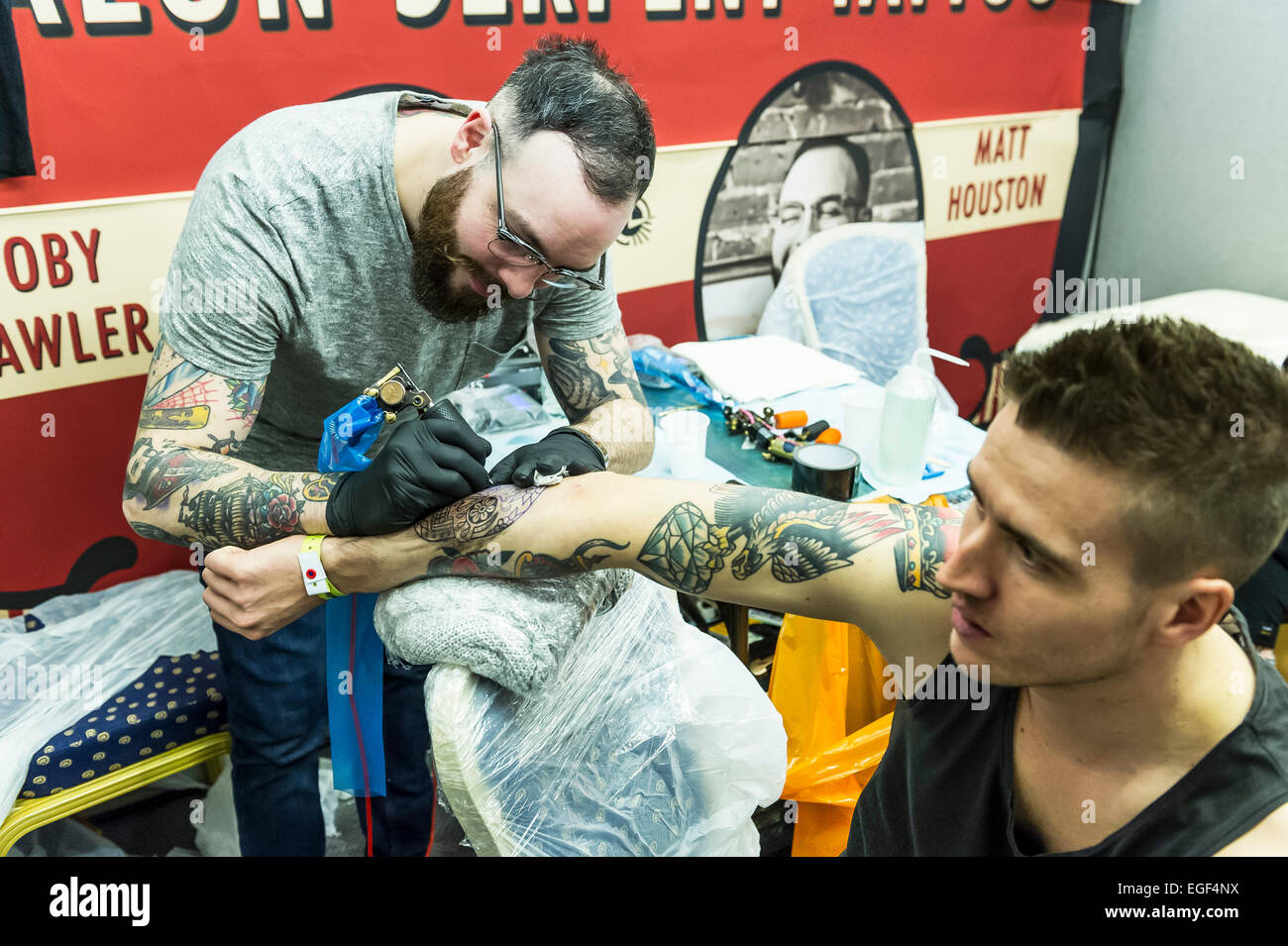 A man being tattooed on his arm at the Brighton tattoo Convention. - Stock Image