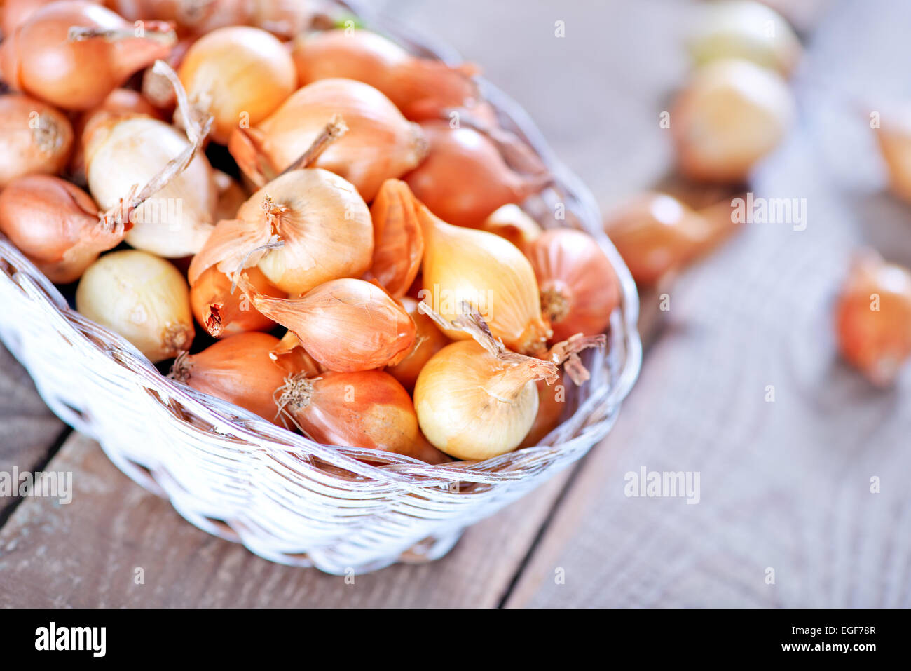 raw onion in basket and on a table - Stock Image