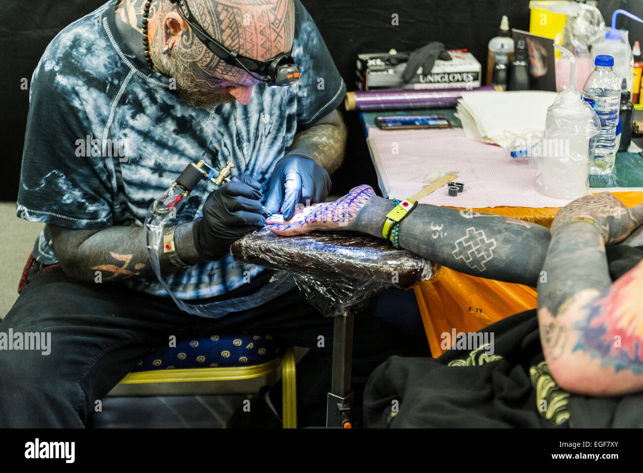 A man being tattooed on the palm of his hand at the Brighton Tattoo Convention. - Stock Image