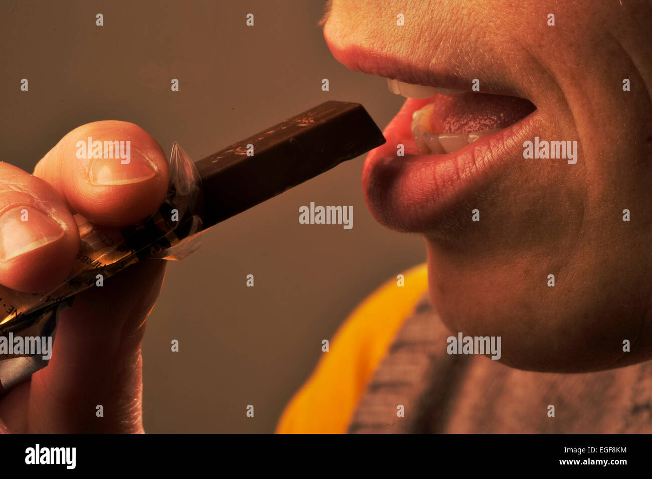 Symbolic picture about sugar in foods: Woman eating chocolate. - Stock Image