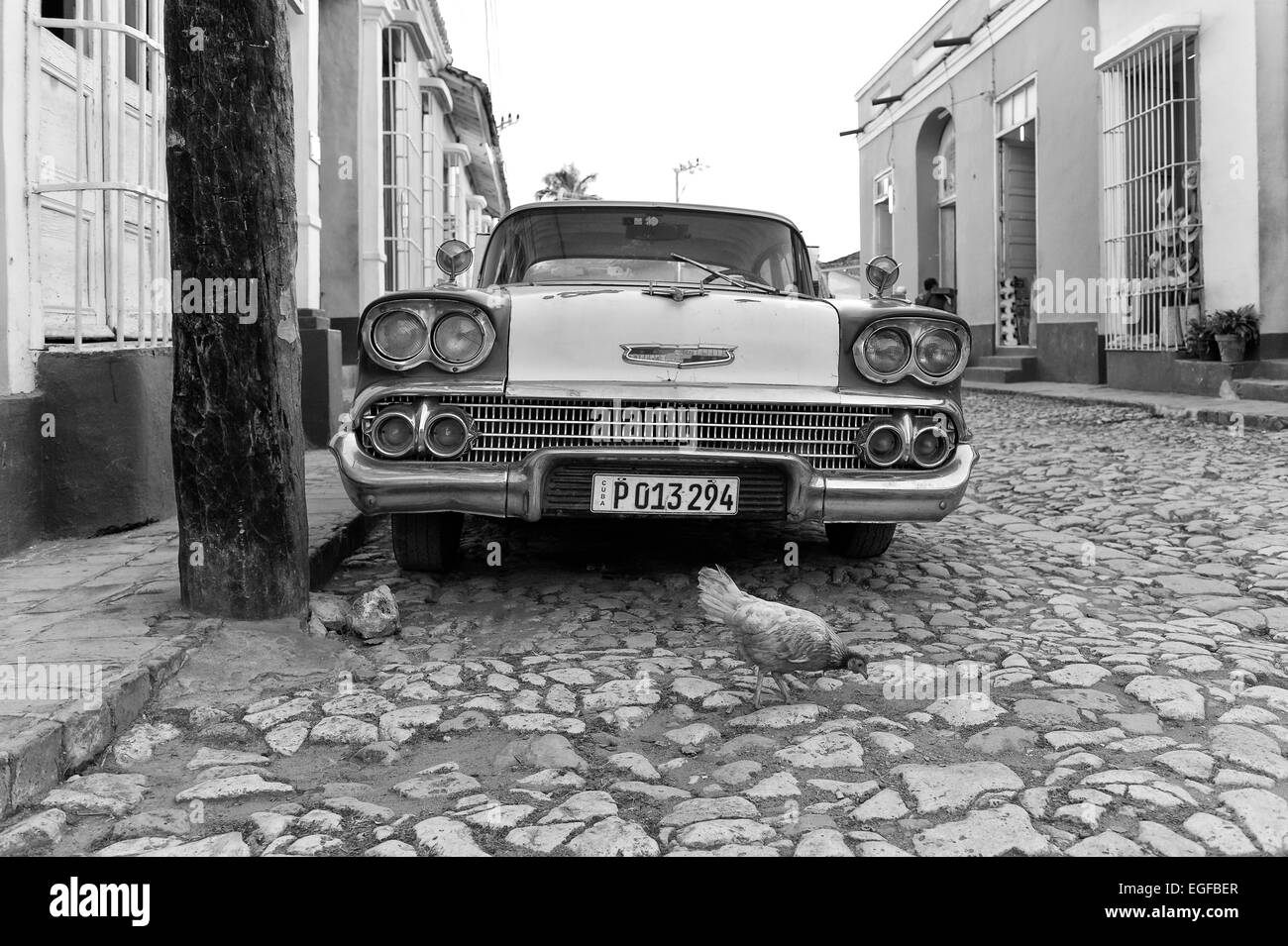 A Cuban classic car parked in a central Trinidad street and a chicken crossing the road. Cuba. - Stock Image