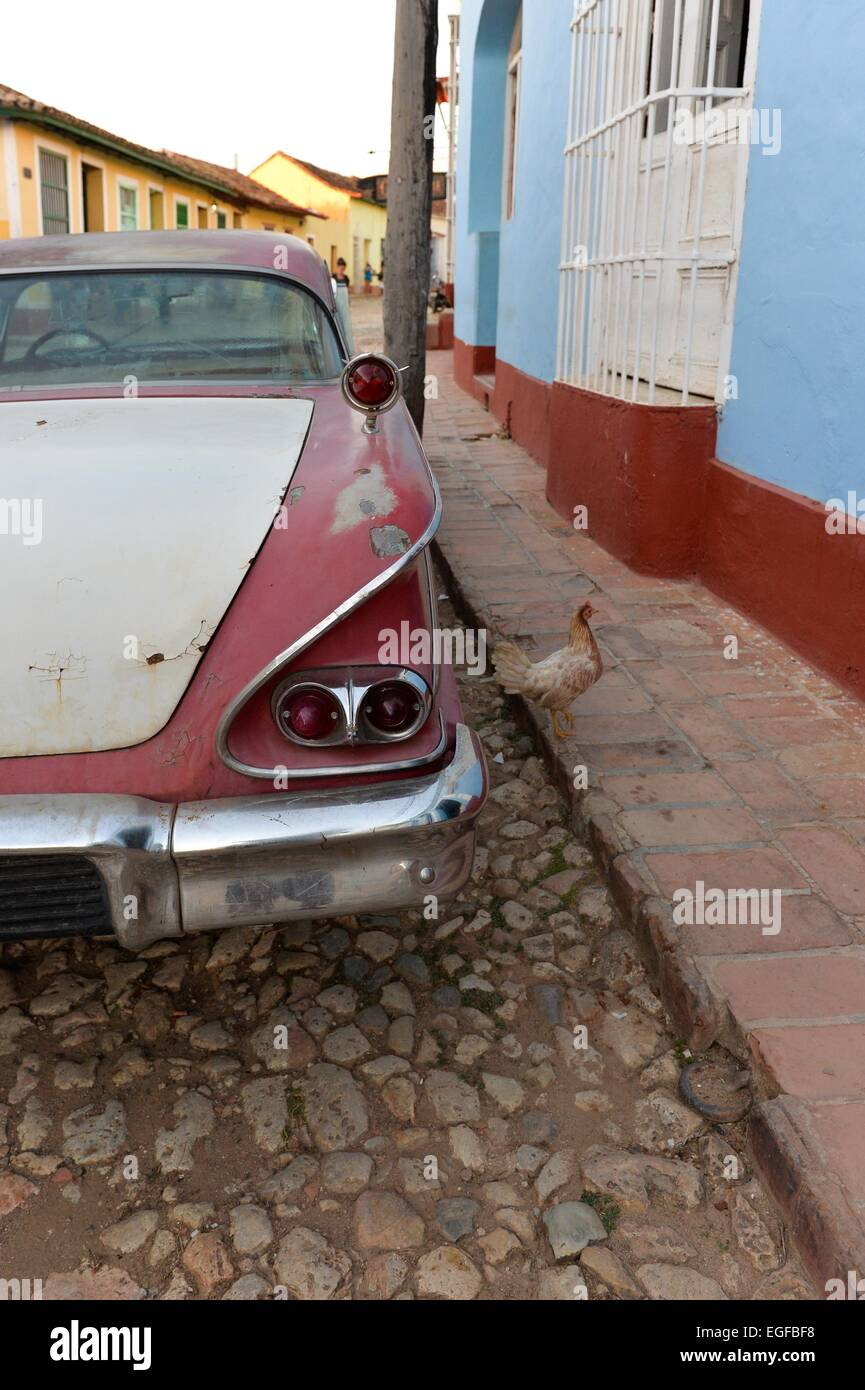A Cuban classic car seen in detail parked in a central Trinidad street and a chicken on the sidewalk. Cuba. - Stock Image