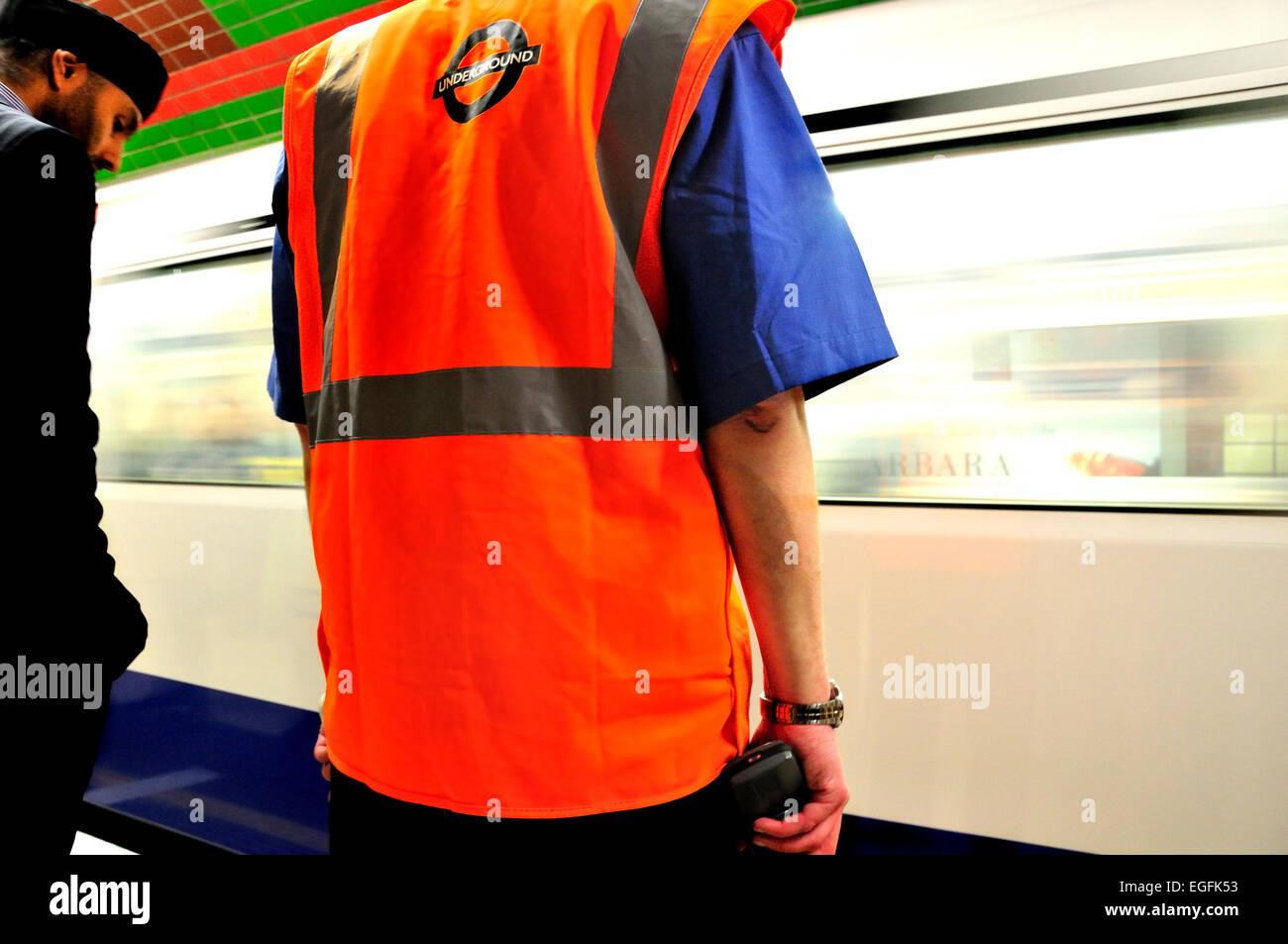 London, England, UK. London underground / tube station employee and passenger on the platform - Stock Image