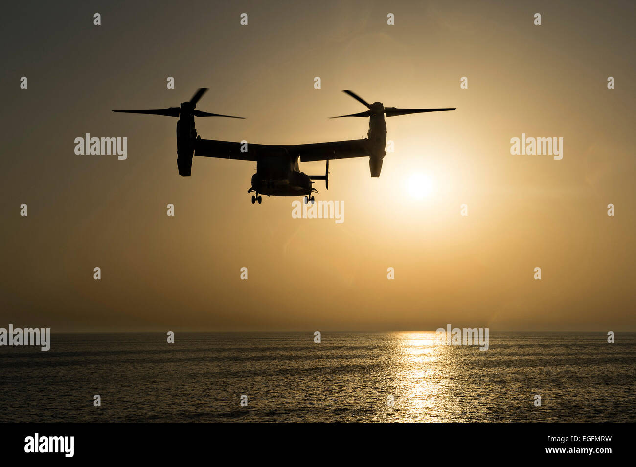 A US Marine Corps MV-22B Osprey tilt rotor aircraft prepares to land on the flight deck of the amphibious transport - Stock Image