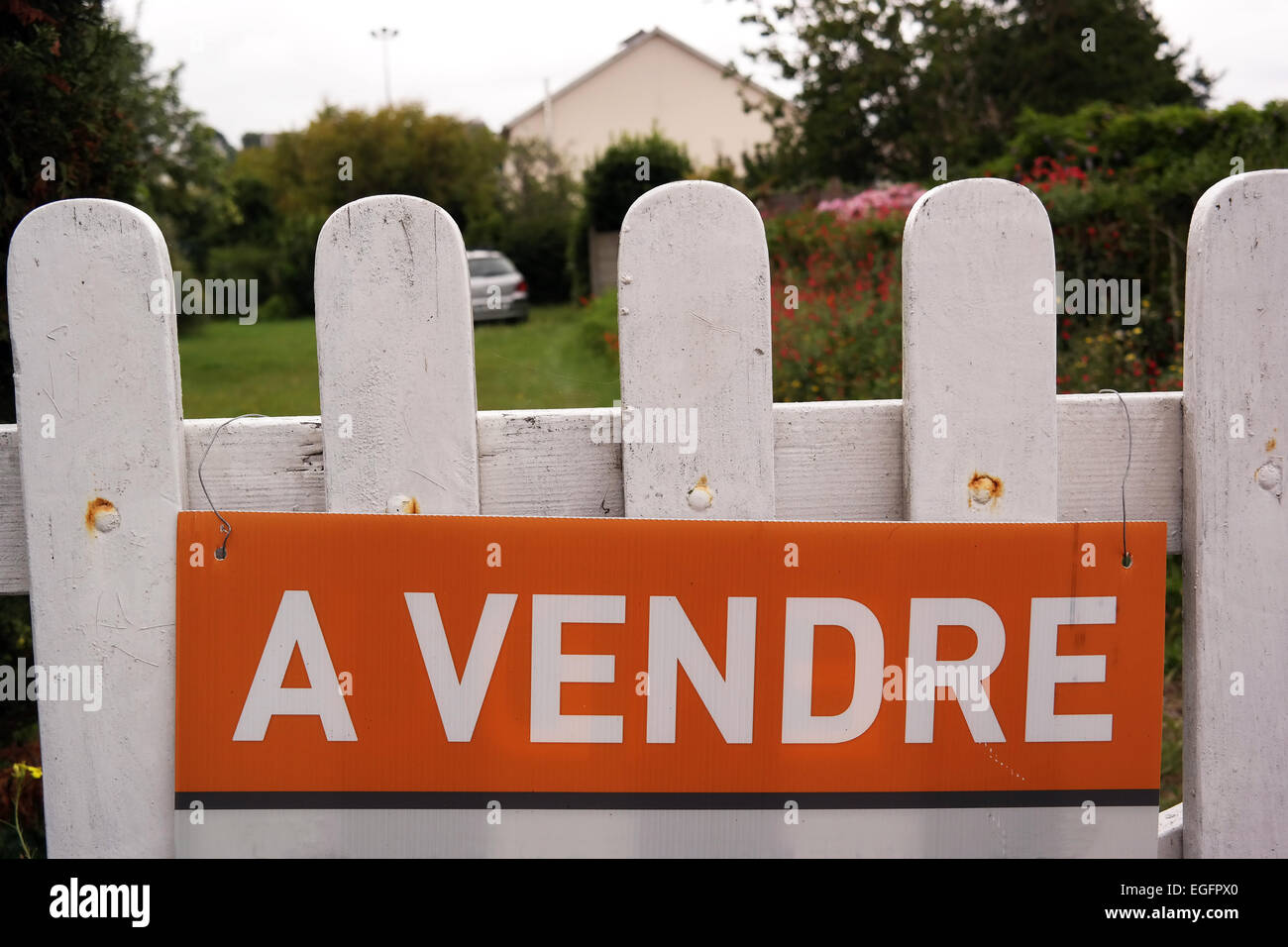 House for sale sign at a fence of a french home in Brittany, France - Stock Image