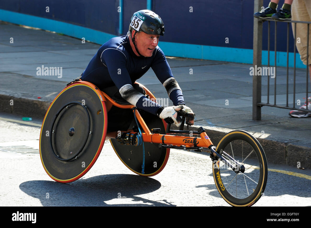 Disabled athlete taking part in the London marathon wheelchair race - Stock Image