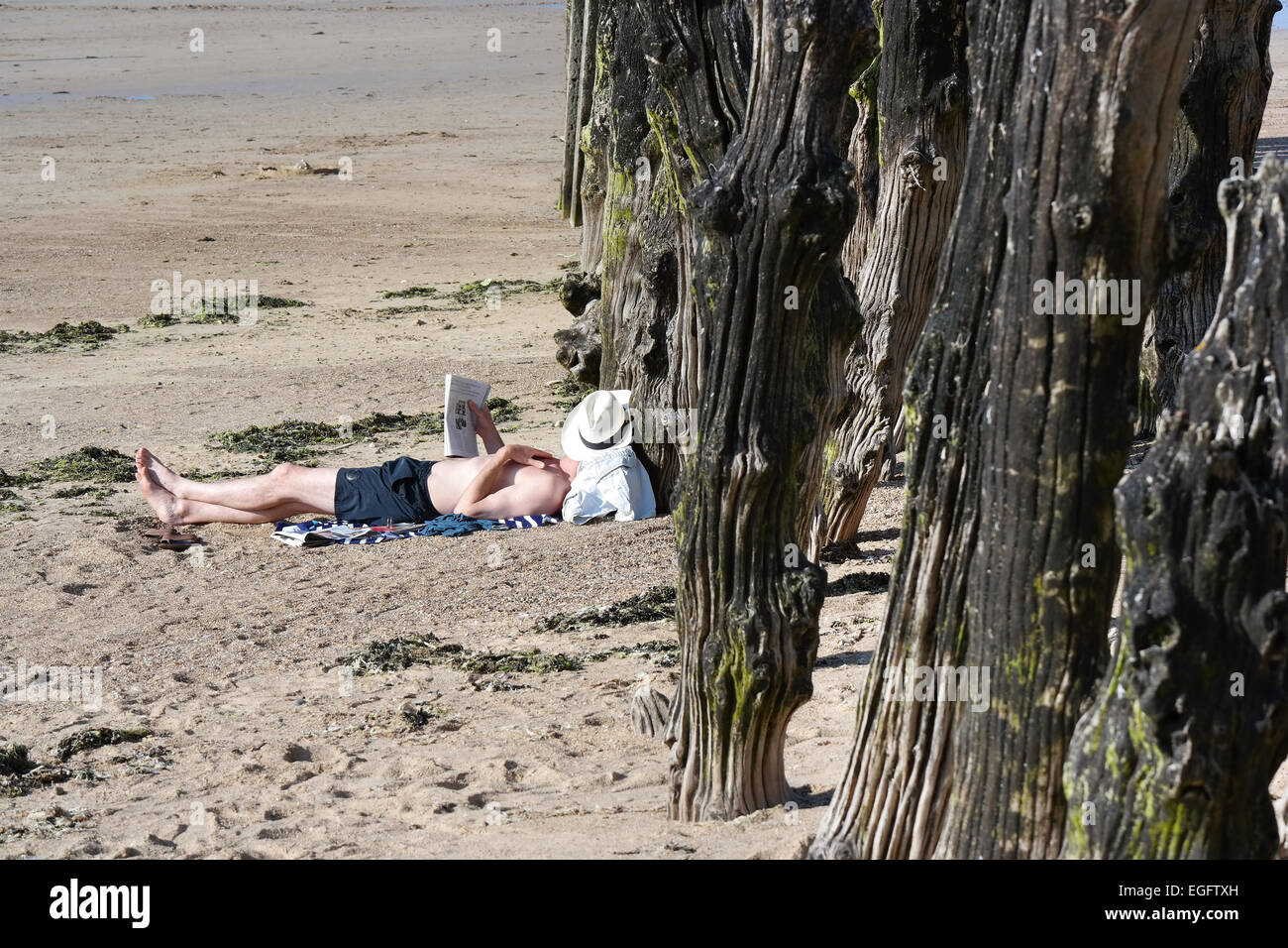 Man with straw hat relaxing and reading a magazine on the beach in Saint-Malo, Brittany, France - Stock Image